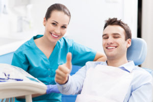 Man in dental chair next to dental hygienist