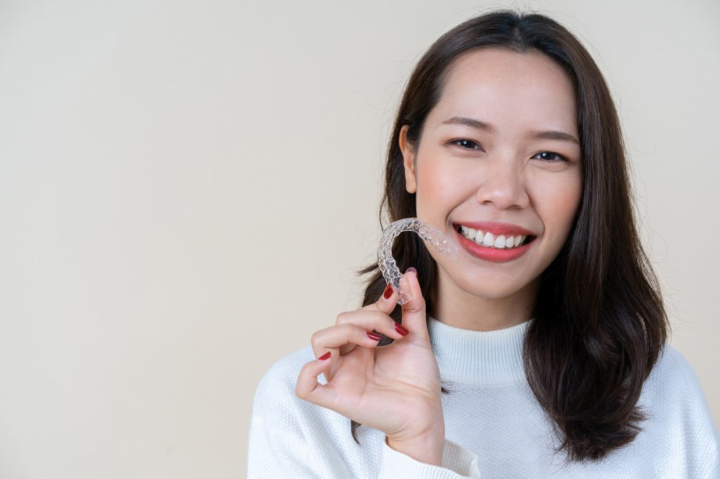 Woman being treated with Invisalign in Sunnyvale is holding a clear aligner tray