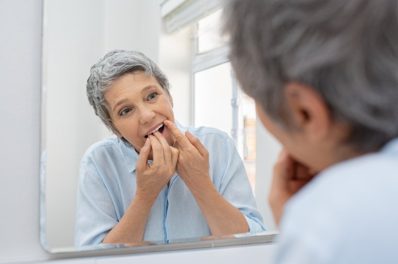 Mature woman with dental implants flossing