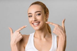Woman confidently smiling while pointing to her teeth